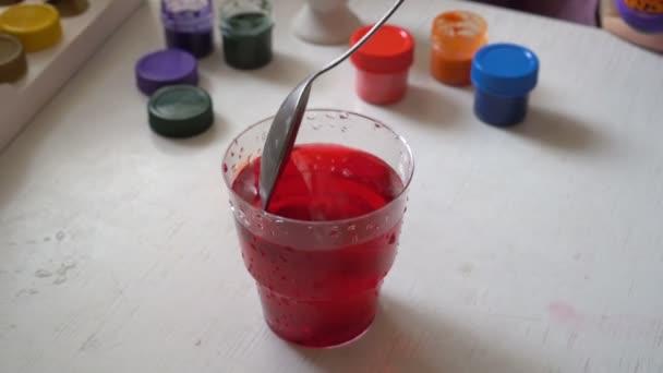 Rodina se připravuje na Velikonoce, dítě barvy vejce ve sklenici s červenou barvou. Zblízka. Pohled shora. 4 k. 25 snímků / s