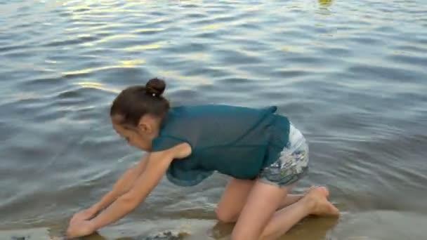 Ein kleines Mädchen spielt bei Sonnenuntergang am Strand und baut auf dem Hintergrund ruhigen Wassers einen Sandturm. Porträt. Nahaufnahme. 4k. 25 fps.
