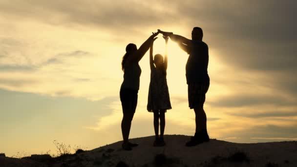 Šťastná rodina: matka, otec a malá dcerka proti dramatické obloze na vrcholu kopce. Rodiče si postavili siluetu domu. Dívčí tanec. Koncept. 4k