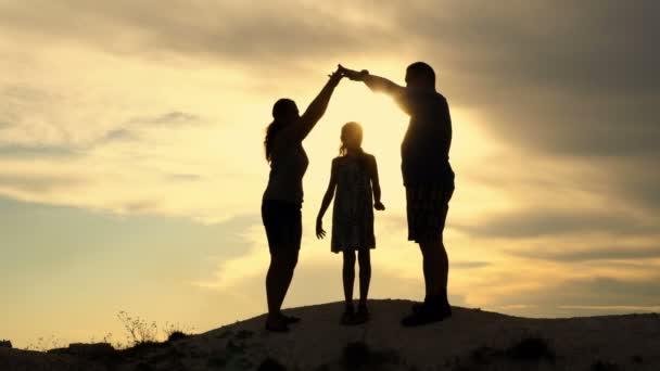 schöne Familie: Mutter, Vater und kleine Tochter im Hintergrund des Sonnenuntergangs auf der Spitze des Hügels. Eltern bauen eine Häusersilhouette über dem Kopf des Kindes. das Konzept einer glücklichen Familie. 4k.