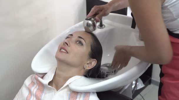 Promytí prádla v tmavém kadeřnictví. Kadeřník nalévá vodu ze sprchy, Pere pěnu a jemně je stlače. Portrét. 4k.