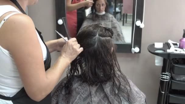 Gyönyörű lány ül a szépségszalonban egy széket előtt egy tükör. Fodrászatok hajszál haját. Közeli. Hátulnézet. 4k.