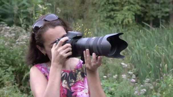 Nahaufnahme des Gesichts einer Fotografin, die bei Sonnenuntergang an einem Sommertag im Park eine Kamera mit einem großen Objektiv aufnimmt und mit jemandem hinter den Kulissen spricht. Porträt. 4k