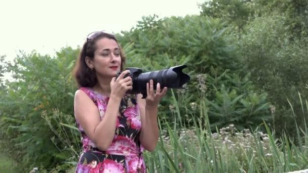 Portrét dívčí fotografa v práci. Fotografuje s profesionálním fotoaparátem s teleobjektiv v parku při západu slunce v letním dnu a mluví s někým, kdo se nachází za scénami. Pohled ze strany.