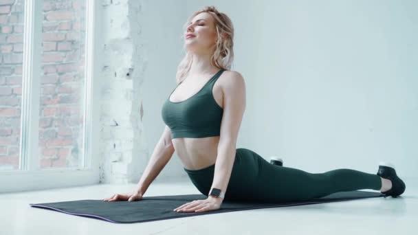 Soustředěná blondýnka si doma u okna procvičuje ranní cvičení na žíněnce. Žena dělá cvičení zad, pilates koncept
