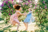 young twin sisters in different dresses having fun in blooming summer botanical garden