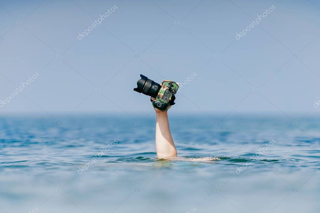 cropped shot of man holding professional photo camera in waterproof case above water