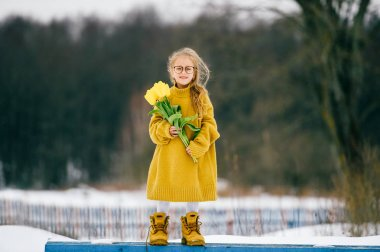 little girl in oversized yellow woollen sweater with yellow tulips outdoors