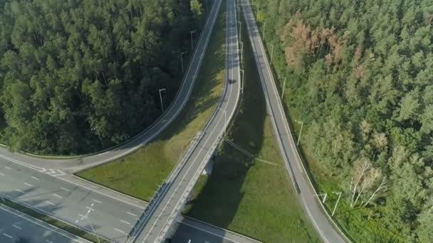 Letecký snímek dálniční nadjezd v hlubokém lese. Létající DRONY zpětně, po černé auto. Zelené borové dřevo