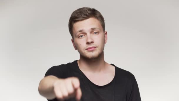 Young man pointing finger at camera. Isolated gray background