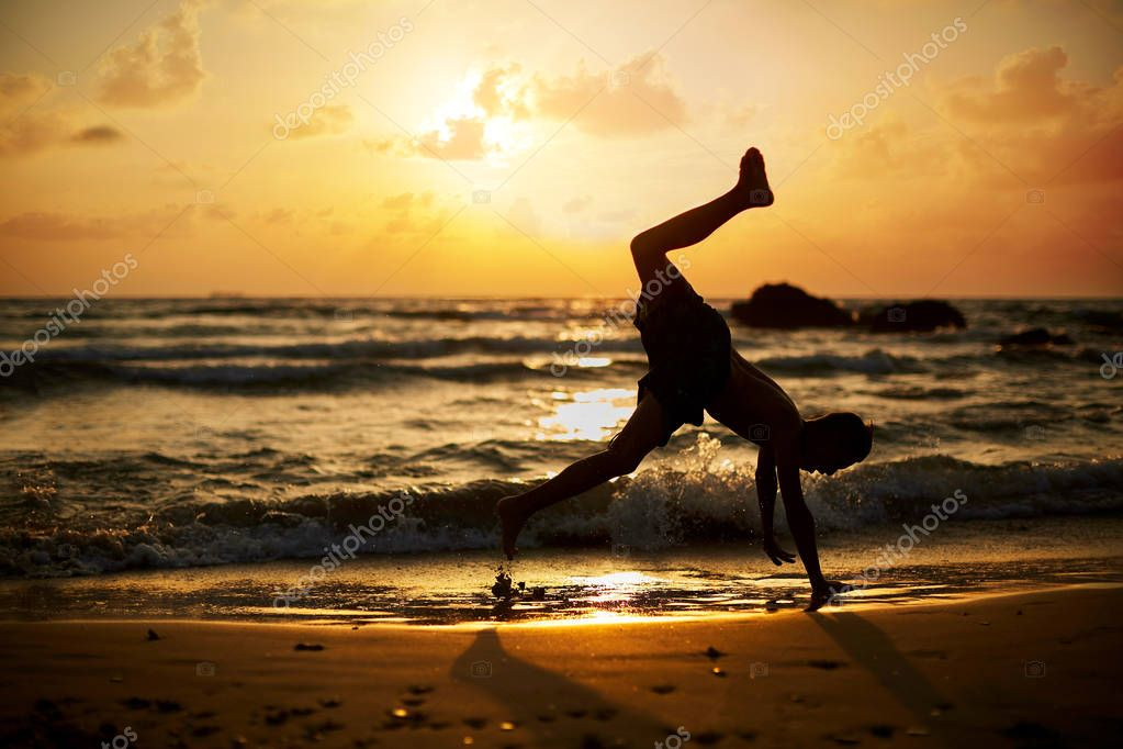 Young boy play capoeira at the beach