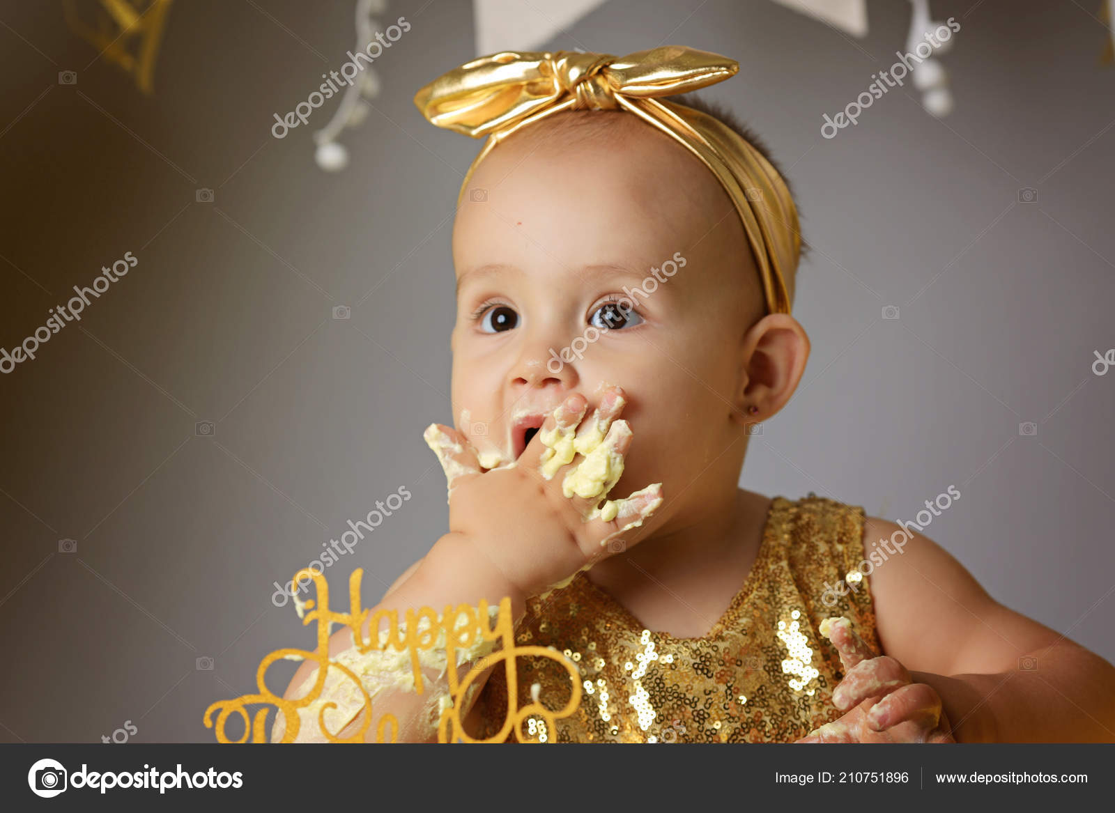 Small Sweet Baby Girl In A Golden Dress With A Bow On Her Head