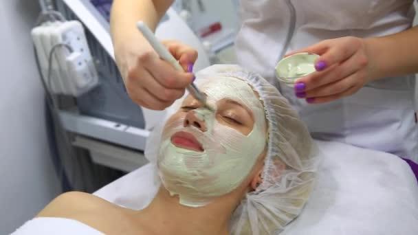 Frau nimmt Gesichtsmaske und genießt sie im Wellness-Salon. fullehd