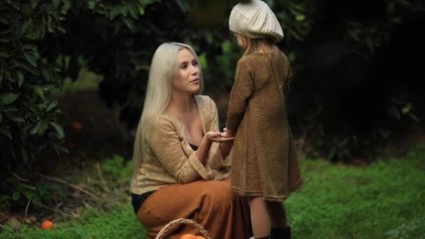 Boční pohled milující matky s holčičkou na zelené louce s košíkem ovoce v zelené sunny sadu. plné hd Slow motion