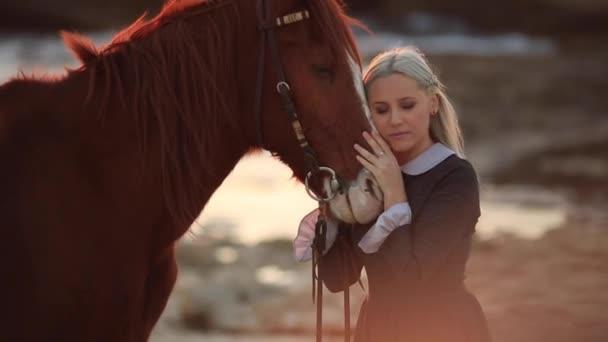 Mladá blondýnka v retro šaty při západu slunce na pozadí moře, starat se o svého koně, pomalý pohyb