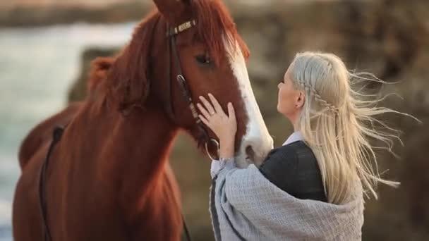Fiatal gyönyörű lány gyaloglás a ló a tengeren
