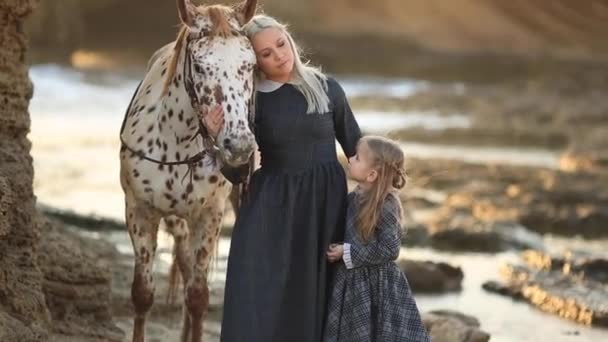 Therapy with horses. Family vacation. Woman with her daughter taking care of her horse