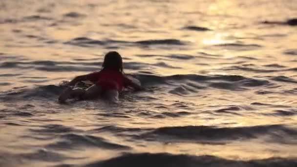 little girl surfer swims forward full HD slow motion