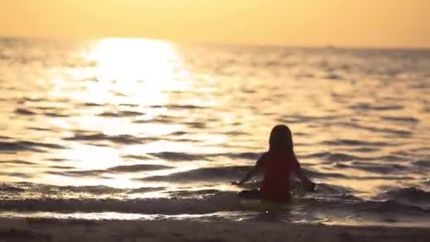 little girl wants to sit on the surfboard