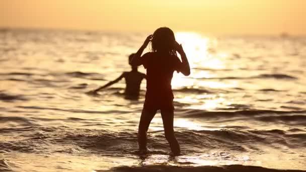 Šťastné děti hrají na pláži při západu slunce. Koncept přátelská rodina