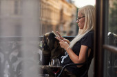 woman drinks red wine, reads social networks, chatting and likes her cell phone