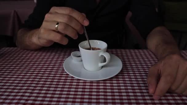 A hangsúly a férfi kezében kanalat a csésze kávé