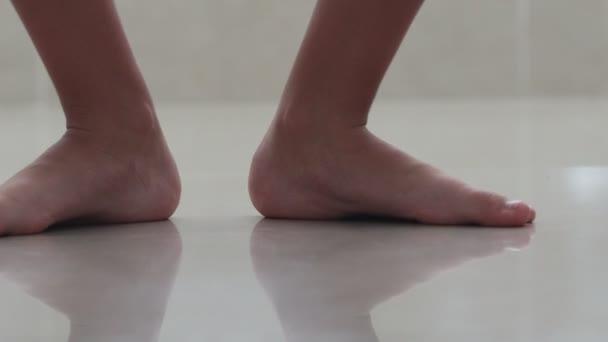 bosé nohy chlapce skákající po dlaždicích různými směry.