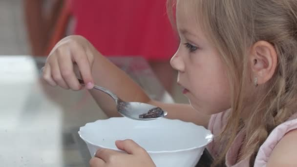 girl eats chocolate cereal with milk
