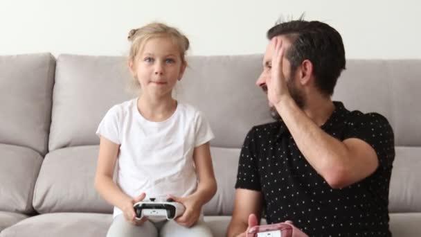 apa és az ő aranyos kis lánya játszik játék konzolt, és mosolyogva ülve heverő