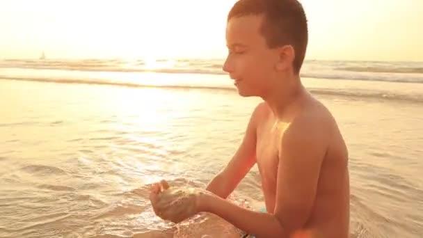 Zeitlupe. Schöne Aussicht auf einen neunjährigen Jungen, der bei Sonnenuntergang oder Sonnenaufgang eine Sandfestung an der Küste baut. Die Oberfläche des Meeres glitzert in goldener Farbe mit orangefarbener Tönung