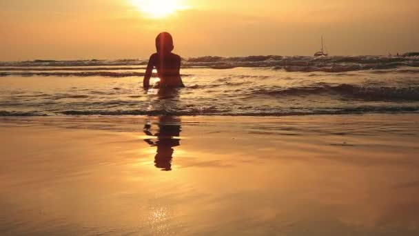 Zeitlupe. Schöne Aussicht auf einen neunjährigen Jungen, der bei Sonnenuntergang oder Sonnenaufgang eine Sandfestung an der Küste baut. Die Oberfläche des Meeres glitzert in goldener Farbe mit orangefarbener Tönung.