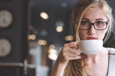 Coffee is the best way to start my day successful. Closeup shot of attractive young woman holding a cup of coffee and looking at camera.