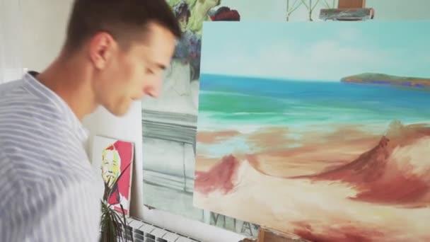 male painter paints landscape on canvas