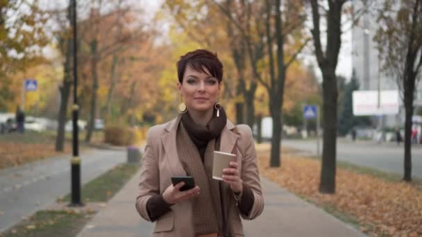 young woman walking down street and using smartphone