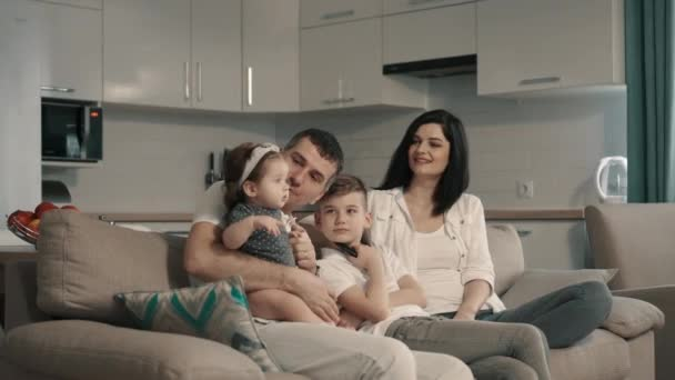 Šťastná rodina sleduje televizi doma na gauči