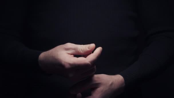 Male hand making money asking sign gesture rubbing fingers together on black background