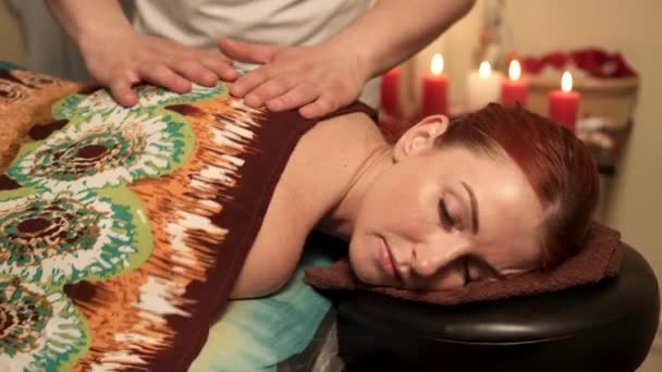 Male massage therapist prepares client woman for massage by heating her muscles in spa salon.