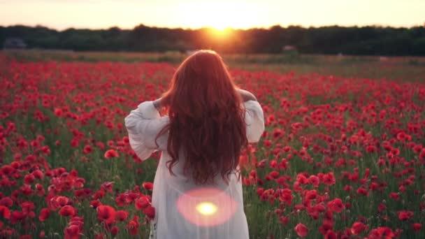 Mladá rudovlasá žena při západu slunce hází vlasy do vzduchu v kvetoucích polích, pomalý pohyb