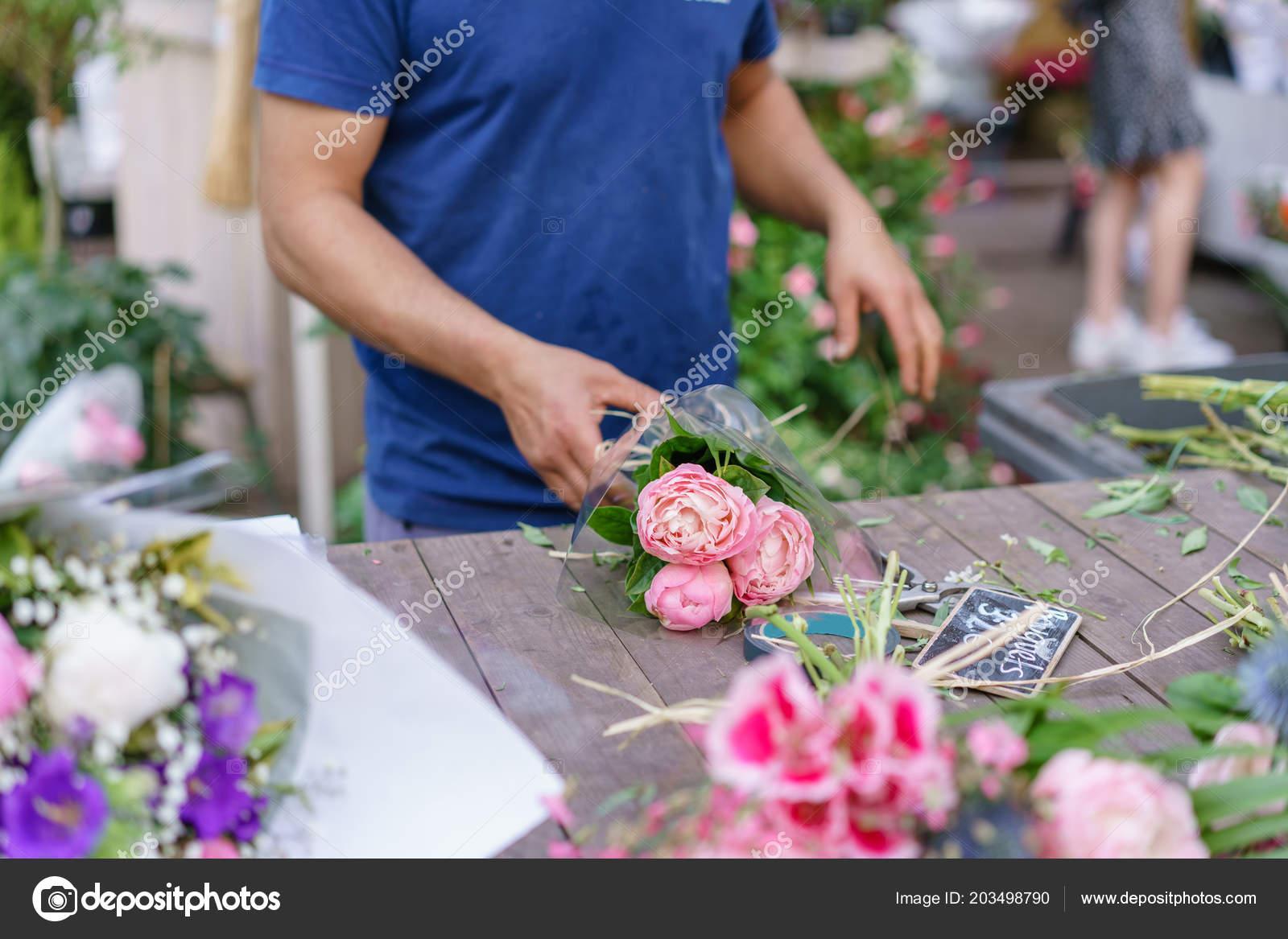 Male florist creating beautiful bouquet in flower shop. outdoor ...