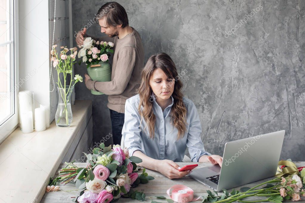 The concept of working in a flower shop. Order-taking and delivery. Woman owner and man assistant in floral design studio, making decorations and arrangements.