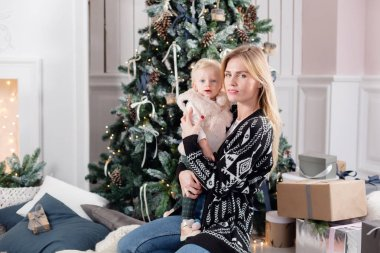 Cheerful mom embraces her cute baby daughter . Parent and little child having fun near Christmas tree indoors. Loving family Merry Christmas and Happy New Year