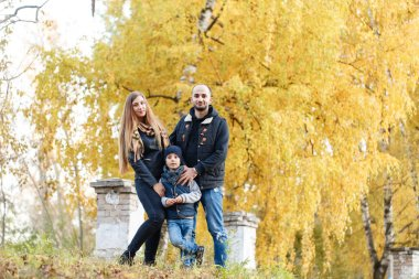 happy family, mom and dad embrace his son in the park. Walk of Bright autumn day. Trees with yellow foliage. Warm october