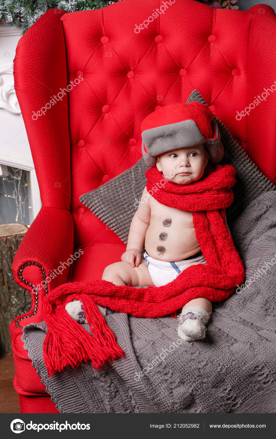 d9b4a01d8d43 Little boy sitting on a red chair in a hat and scarf