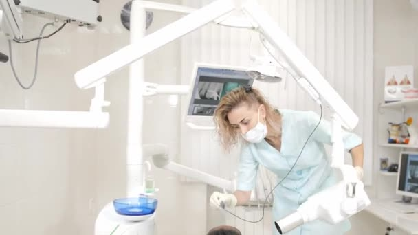 Woman dentist using x ray machine, patient lying on chair in dentistry. Young African American male with bad teeth. Medicine, health, stomatology concept.
