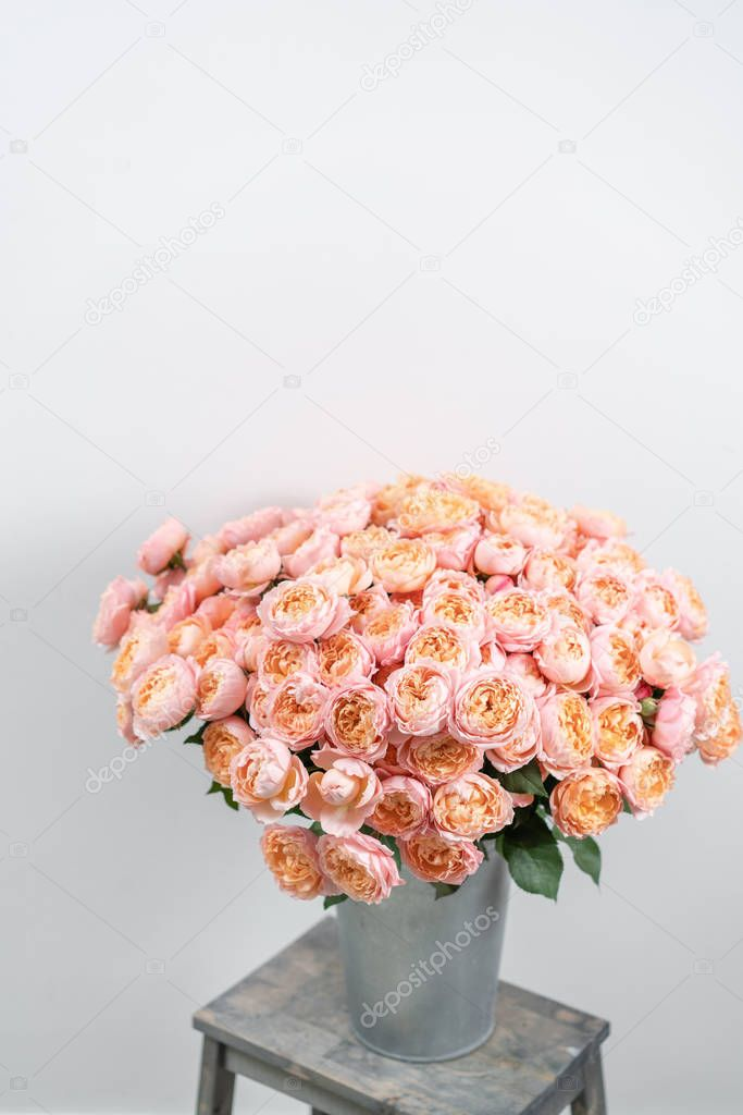Big luxury bright bouquet peony rose on wooden table. Garden spray roses of pink and peach color . bouquet in metal vase