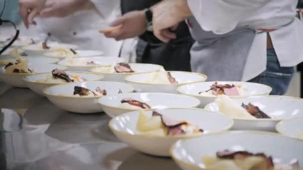 Detailní řádek jídel talířů. Skupina kuchaři zaneprázdněn v komerční kuchyni v restauraci. Personál v restauraci nebo hotelu kuchyni vaření chutné jídlo, je dekorační misky