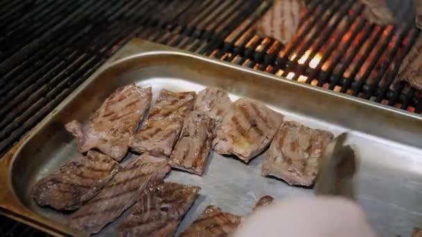 Šéfkuchař má hotové steaky z grilu. Plameny a řeřavé uhlíky argentinského grilu. Příprava oheň a gril pro grilování v restauraci. Steak house, Kobe hovězí maso, ribeye steak.