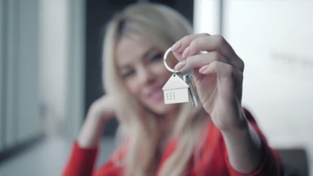 Hypothek-Konzept. Frau im roten Anzug Taste mit Haus geprägt Schlüsselanhänger. Moderne helle Lobby Interieur. Immobilien, Umzug oder Vermietung von Immobilien
