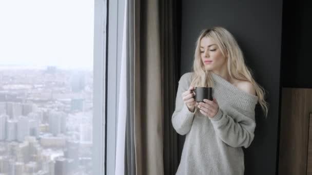 Užijte si krásné blond žena držící keramický šálek čaje nebo kávy. Čas na čaj v pokoji. Při pohledu na okna a pití čaje. Dobré ráno. Hezká mladá dívka relaxační. Happy zimě koncept.