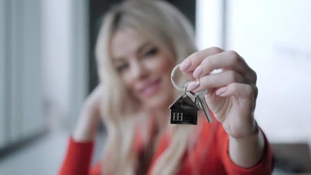 Hypothek. Hypothekenkonzept. Frau im roten Business-Anzug mit Schlüsselanhänger in Hausform. modernes helles Lobbyinterieur. Immobilien, Umzug oder Vermietung.